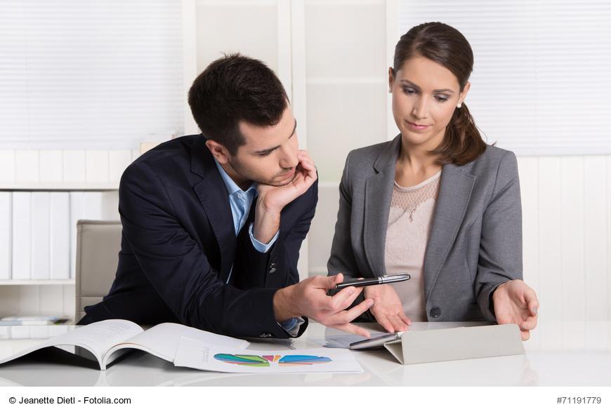 Geschftsleute sitzend im Bro analysieren die Kostensituation
